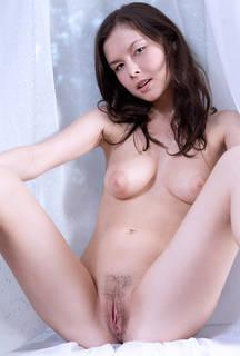 Menina nua com vulva cabeluda.